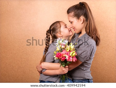 daughter gives her mother flowers in the studio, happy mother's day - stock photo