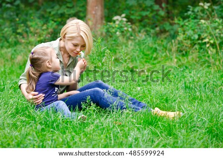 Daughter gives mother a flower smell