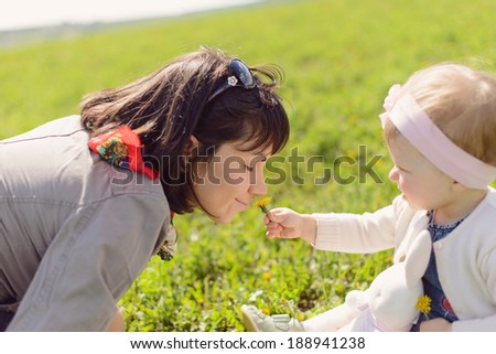daughter giving dandelion her mother to smell  - stock photo