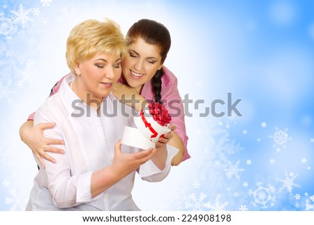 Daughter giving gift to her mother on winter background - stock photo