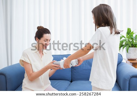 Daughter giving her mother a present at home in the living room - stock photo