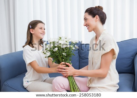 Daughter giving mother white bouquet at home in the living room - stock photo