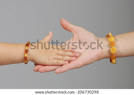 Daughter hand in mother palm on the grey background - stock photo