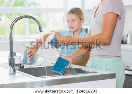 Daughter helping mother do the washing up in the kitchen