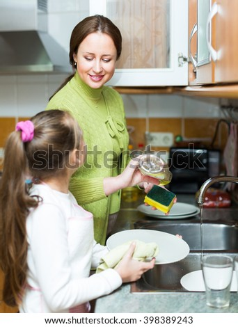 Daughter helping mother washing dishes in the kitchen