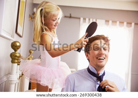 Daughter Helps Father To Get Ready For Work By Brushing Hair - stock photo