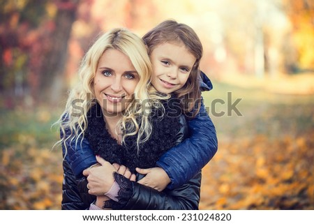 Daughter hugging her mother autumn park - stock photo