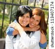 Daughter hugging her mother outdoors happy loving teen bonding affectionate - stock photo