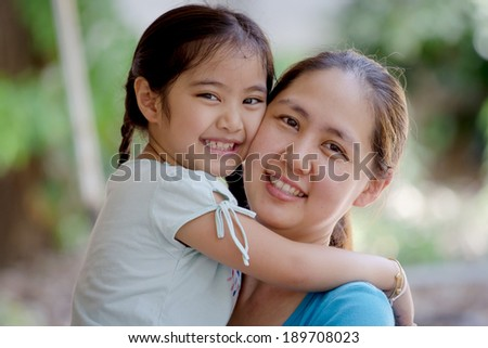 Daughter hugging mother Asian family