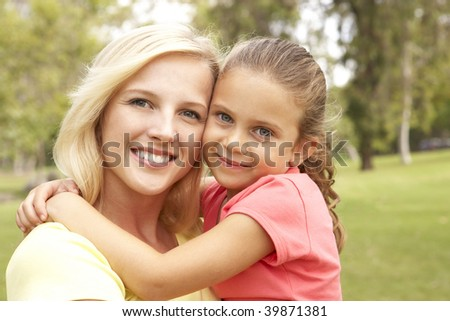 Daughter Hugging Mother In Park - stock photo