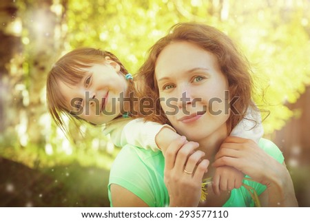 Daughter hugging mother on a bright sunny day.