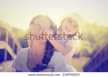 Daughter hugging mother on nature.