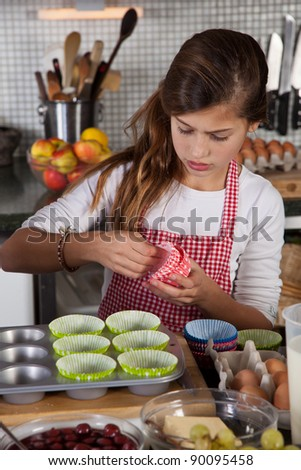 Daughter is making cupcakes in kitchen - stock photo