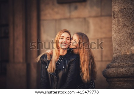 daughter kissing her mother in the city - stock photo