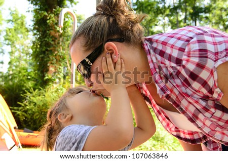 daughter kissing mom on camping trip