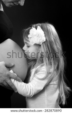 Daughter kissing pregnant mothers belly - stock photo
