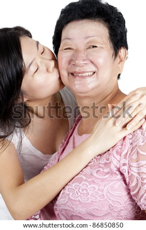 Daughter kissing to her mum. - stock photo