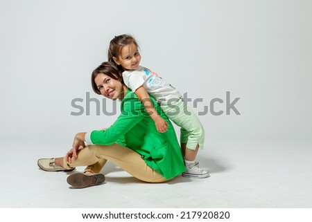 daughter leaned on her mother, who is sitting on the floor - stock photo