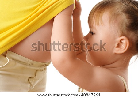 Daughter looking at pregnant mother's belly, isolated over white - stock photo