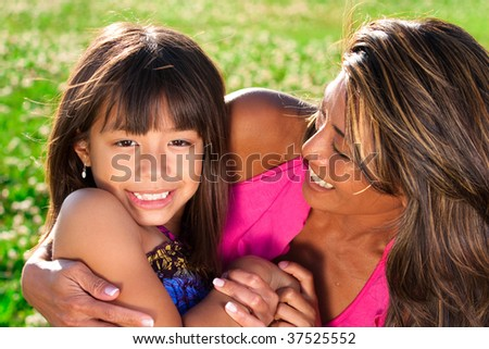daughter looking into camera as her mom smiles at her - stock photo