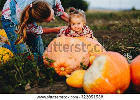 daughter lying on a pumpkin, and her mother standing beside, Halloween eve - stock photo