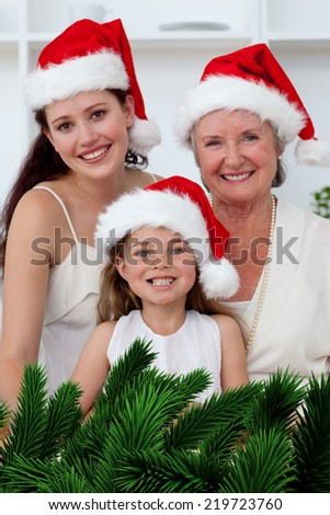 Daughter mother and grandmother baking Christmas sweets against digitally generated fir tree branches - stock photo