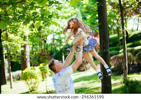 Daughter playing with her father in the park - stock photo
