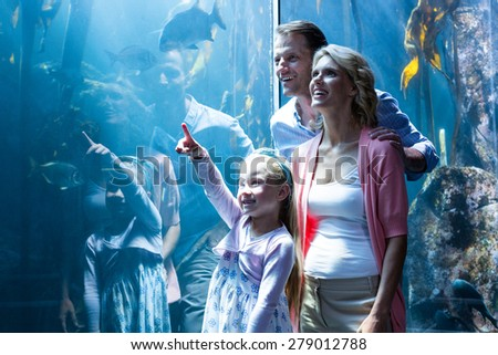Daughter pointing a fish while her mother and father looking at fish tank - stock photo