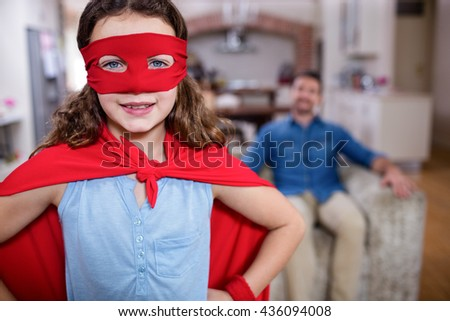 Daughter pretending to be a superhero while father sitting on sofa at home - stock photo