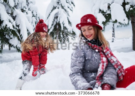 daughter provokes mother play snowballs - stock photo