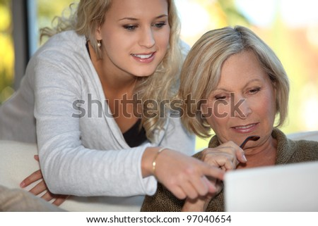 Daughter showing mother how to use  the Internet - stock photo