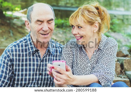 Daughter shows a mobile phone old father  - stock photo