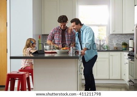 Daughter sits in kitchen while her male parents prepare meal - stock photo