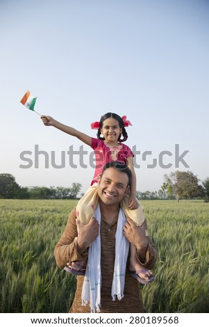 Daughter sitting on father's shoulders with the Indian flag in an agricultural field