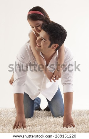 Daughter sitting on her father's back - stock photo