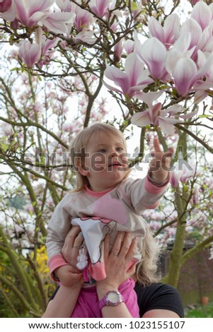daughter sitting on mothers shoulder and picking some leaves of an magnolia tree