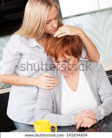 Daughter soothes sad mother. Young woman calm mature woman - stock photo