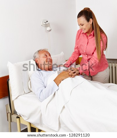 Daughter vising her old father at sickbed in hospital - stock photo