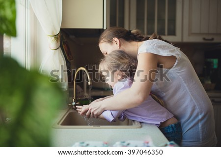 Daughter with her mother to wash their hands in the kitchen sink,. casual lifestyle photo series in real life interior,toning - stock photo