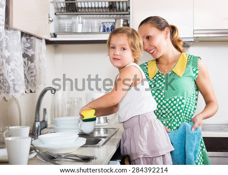 Daughter with mother washing dishes in kitchen