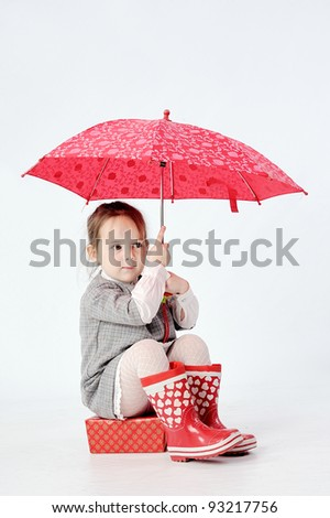 Daughter with red umbrella and bots - stock photo