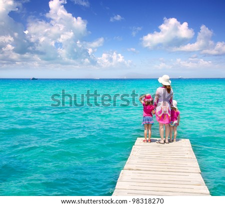 Daughters and mother in jetty on Formentera with turquoise sea [ photo-illustration] - stock photo