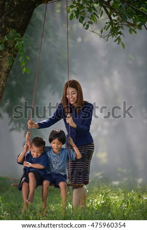 Daughters , my mother and her son on a swing (Focus on Children).