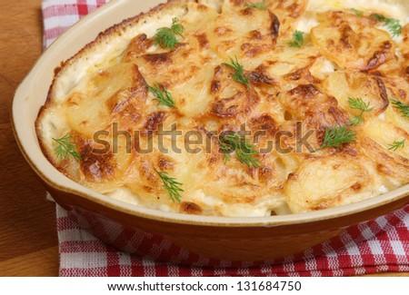 Dauphinois potatoes in ceramic casserole dish. - stock photo