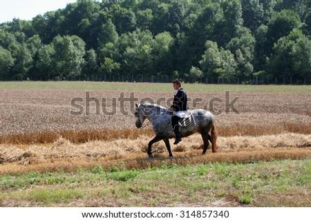 DAVOR, CROATIA - JUNE 26: Men on horseback dressed in national costume, riding through fields of wheat during wheat harvest in Davor, Slavonia, Croatia on June 26, 2010 - stock photo