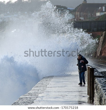 DAWLISH, DEVON, ENGLAND - JAN 7, 2014: An unknown man walking along the sea wall between Dawlish and Dawlish Warren is about to be soaked by a large wave. - stock photo