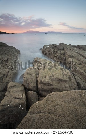 dawn at elgol with sea flowing round rocks on the shore - stock photo