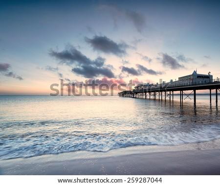 Dawn at the pier on Paignton beach near Torquay in Devon - stock photo