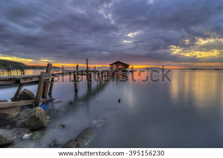 Dawn breaks at wooden fisherman's jetty in Jelutong, Penang Malaysia