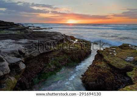 Dawn breathes its first light upon the land as the rhythm of the ocean  brings soothing sounds along the broken shoreline - stock photo